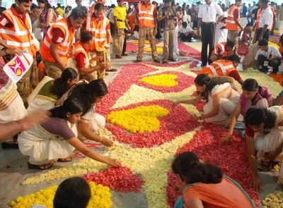Women arranging flowers for pookalam onam